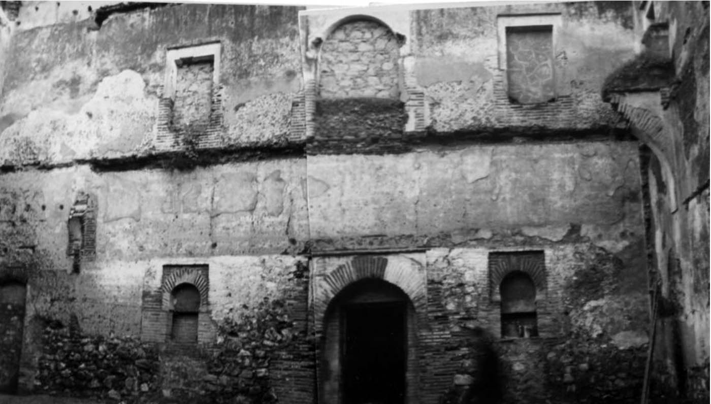 Lámina 20. El lado sur del patio al comienzo de las obras de restauración de 1976. Se aprecian los arranques de la arquería de este costado y los arcos de herradura de ladrillo de las ventanas de la planta baja. Fotografía del archivo de RESGAL.